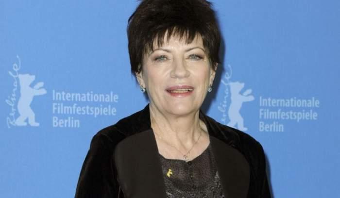 Actrița Luminiţa Gheorghiu a murit la 71 de ani poartă o bluză neagră cu un sacou negru pe deasupra și zâmbește larg. Artista se afla la Festivalul Internațional de Film de la Berlin.