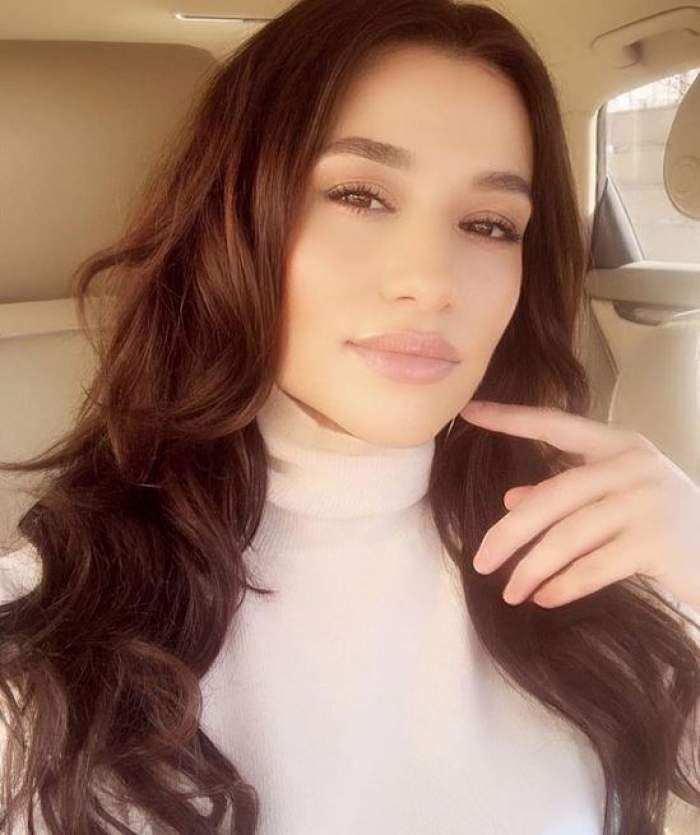 Claudia Pătrășcanu își face un selfie în mașină. Vedeta poartă o maletă albă și își ține un deget la nivelul bărbiei.