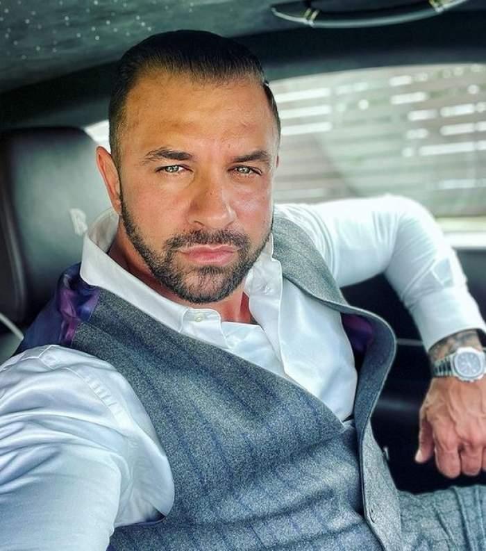 Alex Bodi își face un selfie din mașină, poartă cămașă albă și vestă gri.