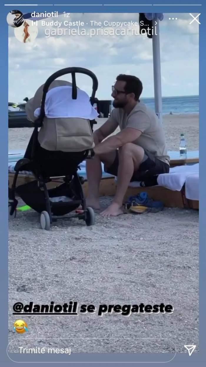 Dani Oțil stă la un șezlong, la mare, și leagănă un copil aflat în căruciorul de bebeluși. Prezentatorul poartă ochelari de soare.