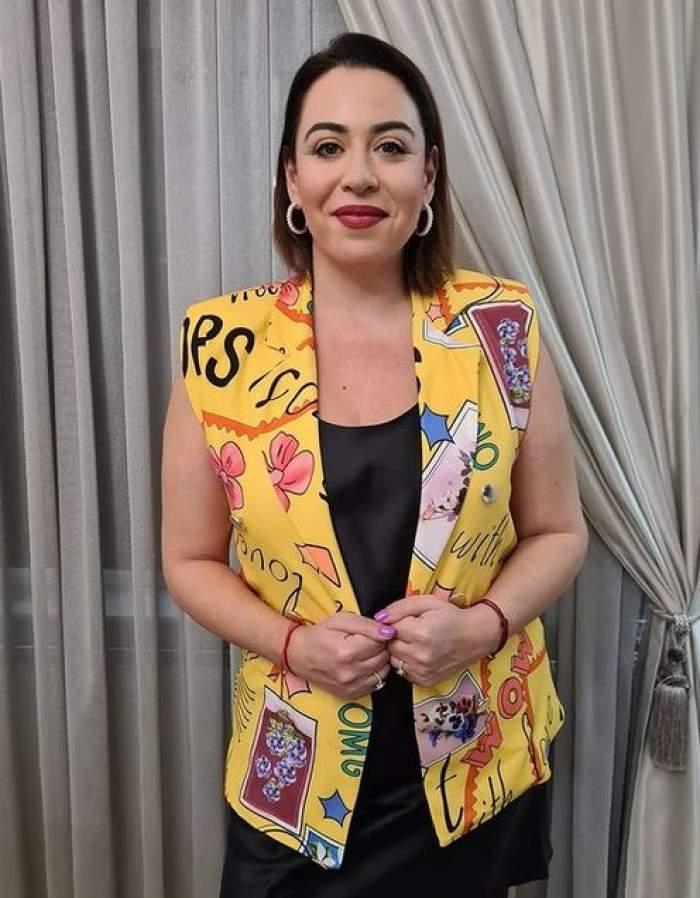 Oana Roman poartă un sacou galben, fără mâneci, tip vestă, cu desene, iar pe dedesubt o rochie neagră. Vedeta zâmbește discret.
