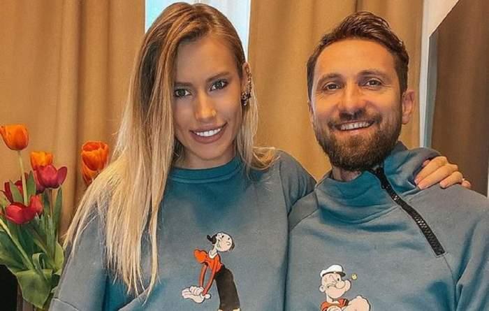 Gabriela Prisăcariu și Dani Oțil poartă amândoi bluze gri. Aceștia zâmbesc și în spatele lor se văd niște lalele în vază.