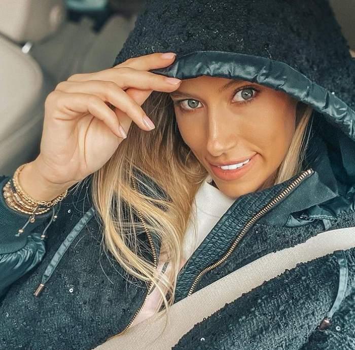 Gabriela Prisăcariu e în mașină. Vedeta poartă o geacă tip hanorac de culoare neagră și își ține gluga pe cap cu ajutorul unei mâini. Iubita lui Dani Oțil zâmbește larg.