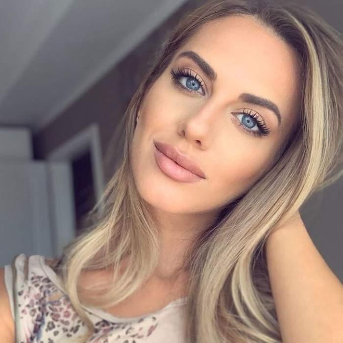 Antonia Ștefănescu își face un selfie, e îmbrăcată în maiou alb și zâmbește discret.