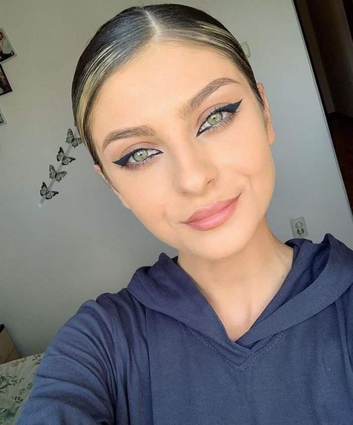 Elena Matei își face un selfie, poartă hanorac albastru, zâmbește slab și are părul prins la spate.