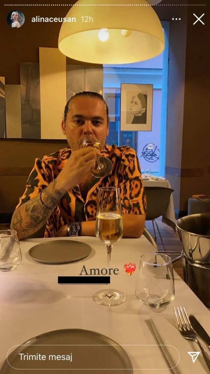 Raul Tisa e la restaurant și bea din pahar. Soțul Alinei Ceușan poartă o cămașă cu animal print, iar deasupra lui e o lampă aprinsă.