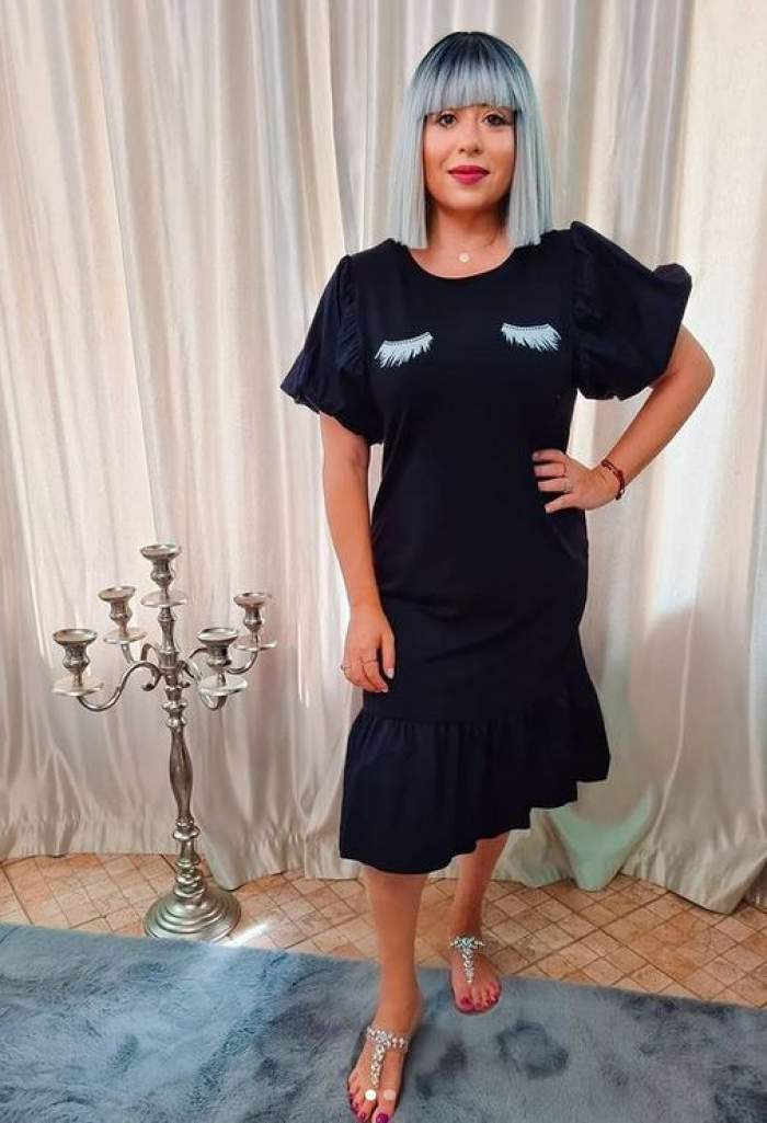Oana Roman poartă o rochie neagră, ține mâna în șold și zâmbește. Lângă ea e un suport de lumânări argintiu.