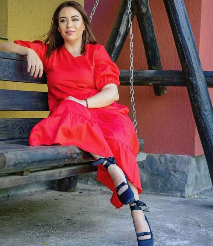 Oana Roman stă pe leagăn, poartă o rochie roșie și opincuțe negre. Vedeta zâmbește slab.