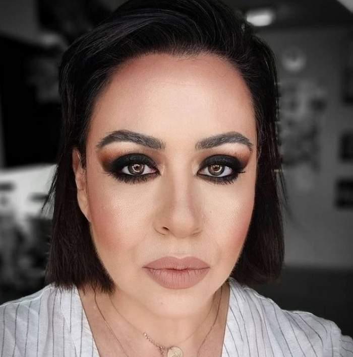 Oana Roman își face un selfie, poartă o bluză albă cu dungi subțiri și e machiată cu nuanțe de negru la ochi.