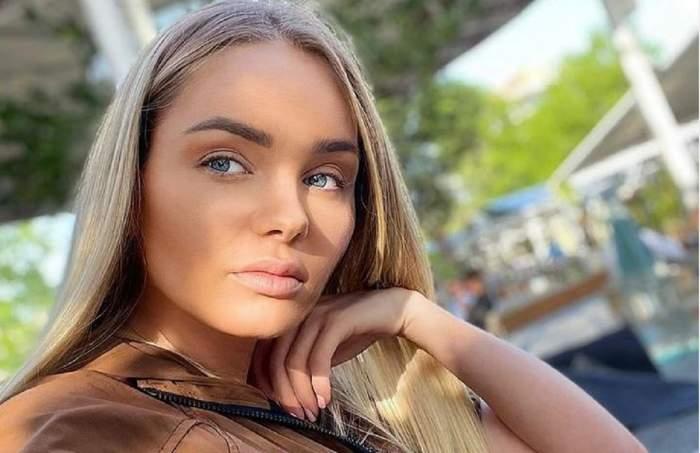 Maria Constantin e la o terasă, își face un selfie și-și susține bărbia cu mâna. Artista poartă bluză maro.