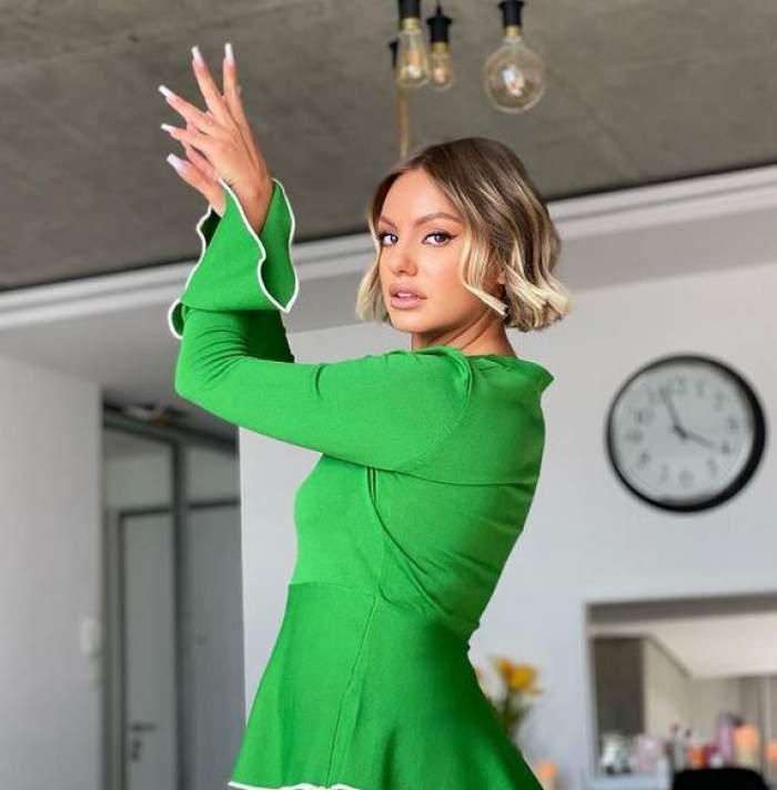 Alexandra Stan e în sufrageria casei, poartă bluză verde și ține mâinile în aer.