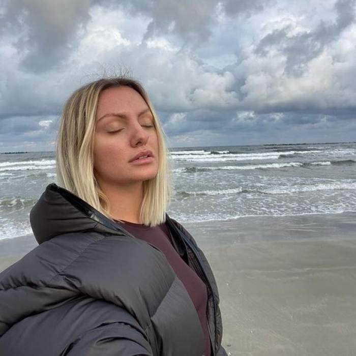 Alexandra Stan e la mare, pe plajă. Vedeta ține ochii închiși și poartă geacă neagră de iarnă.
