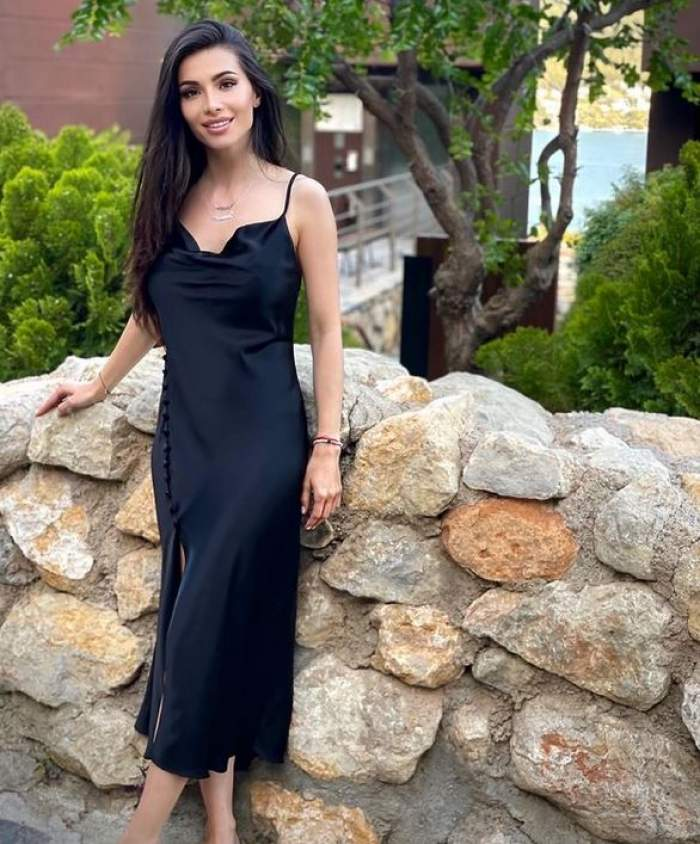 Anda Călin poartă rochie neagră, zâmbește, iar în spatele ei e un zid de piatră.