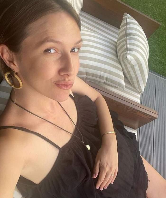 Adela Popescu își face un selfie, poartă o rochie neagră și își ține mâna pe burtica de gravidă.
