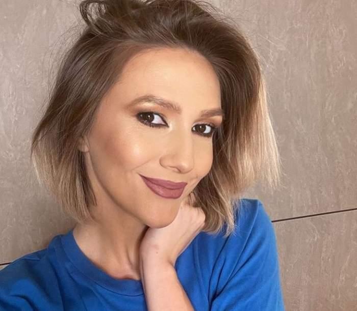 Adela Popescu e îmbrăcată cu un tricou albastru. Vedeta își ține o mână la gât și zâmbește slab.