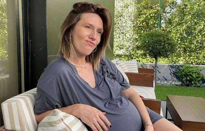Adela Popescu stă pe canapea, pe terasa casei și poartă un tricou larg, gri.