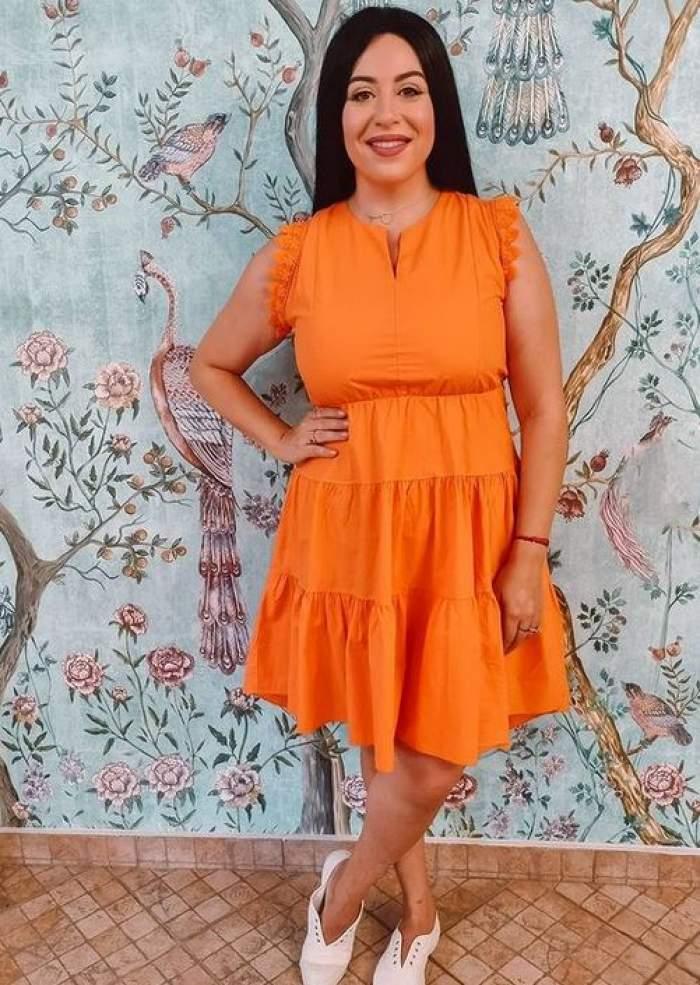 Oana Roman poartă rochie oranj și își ține o mână în șold. Vedeta zâmbește larg.