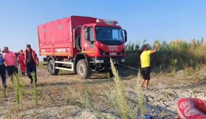 Mașina de pompieri și câțiva oameni pe câmp