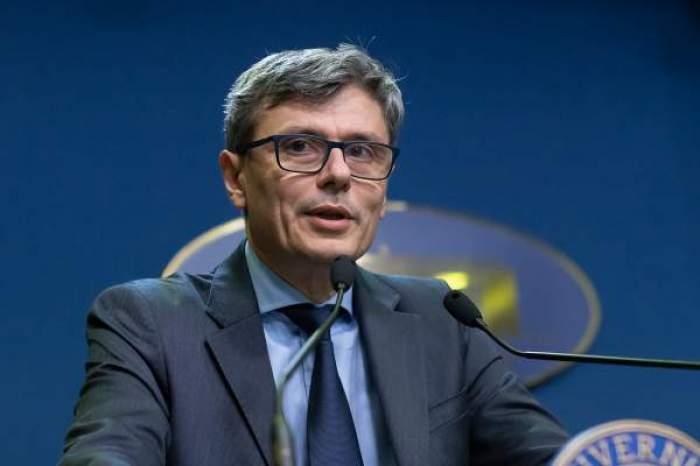 Virgil Popescu, vorbind, în costum albastru