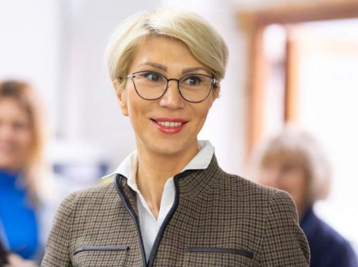 Raluca Turcan, surprinsă zâmbind, îmbrăcată în maro