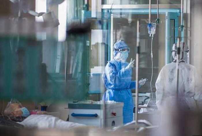 Un medic în combinezon printre pacienți