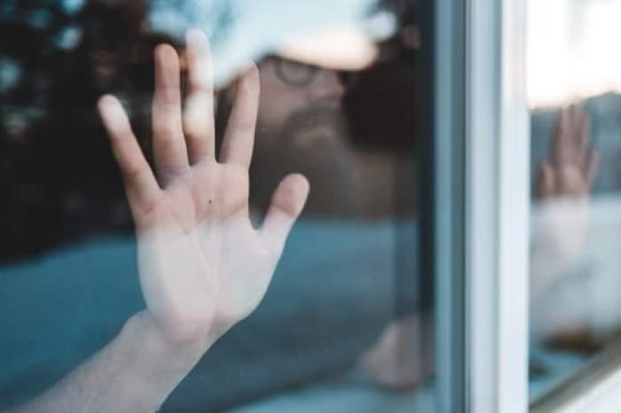 bărbat închis în casă stă la fereastră