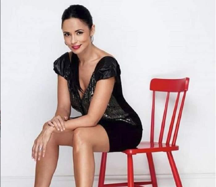 Andreea Marin, în ținută neagră, stă pe un scaun roșu