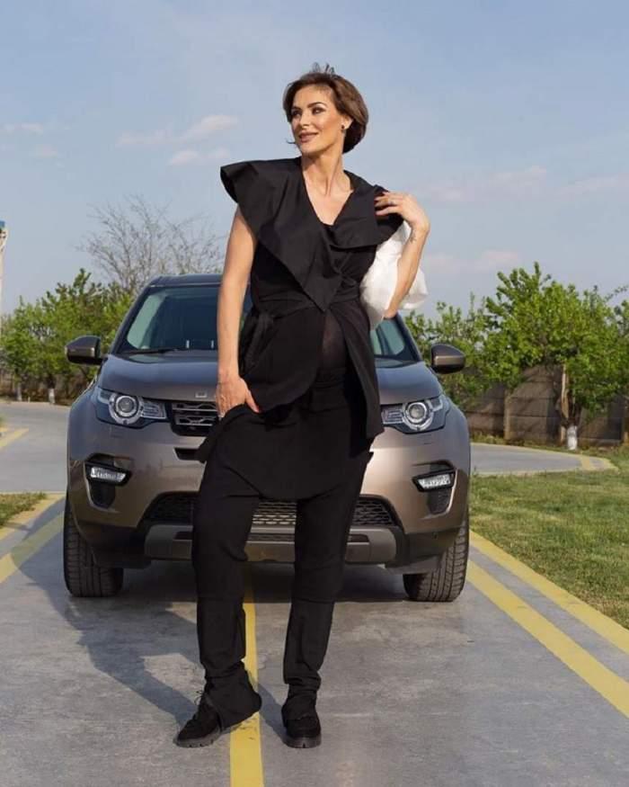 Roxana Ciuhulescu, lângă mașină, îmbrăcată în negru