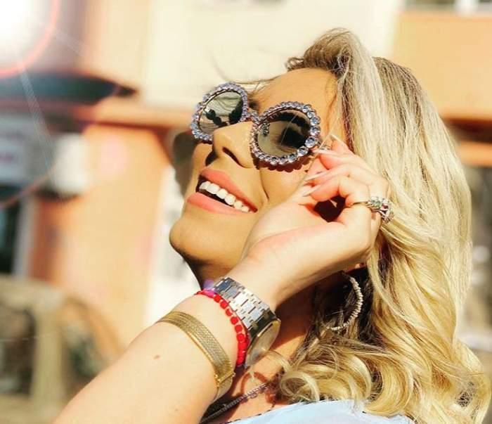 Roxana Diță, zâmbitoare, cu ochelari de soare pe față