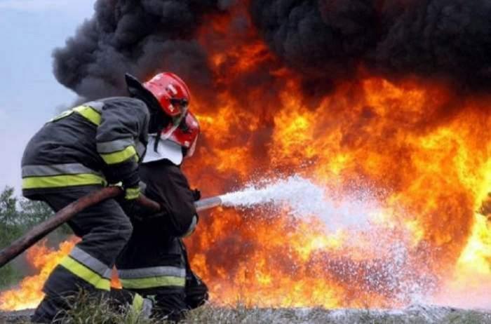 Doi pompieri care sting un incendiu