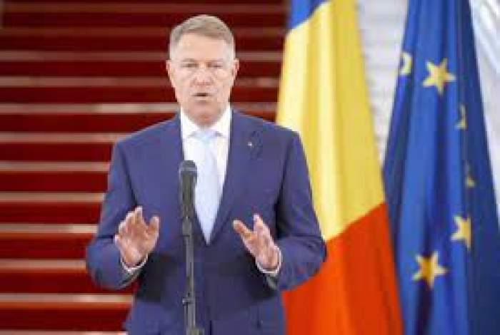 Klaus Iohannis vorbește în cadrul unei conferințe, îmbrăcat în costum albastru, gesticulând