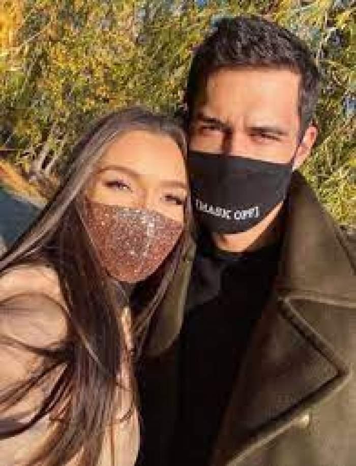 Viviana Sposub și George Burcea, fotografiați îmbrățișați, purtând mască de protecție
