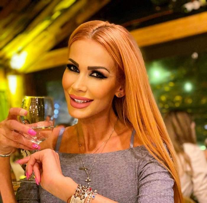 Nico Delinescu, zâmbitoare, cu un pahar de vin în mână
