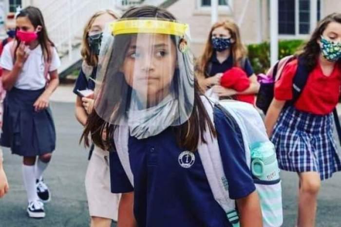 O elevă cu mască de protecție pe față