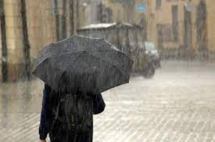 Un om care merge prin ploaie cu mașina