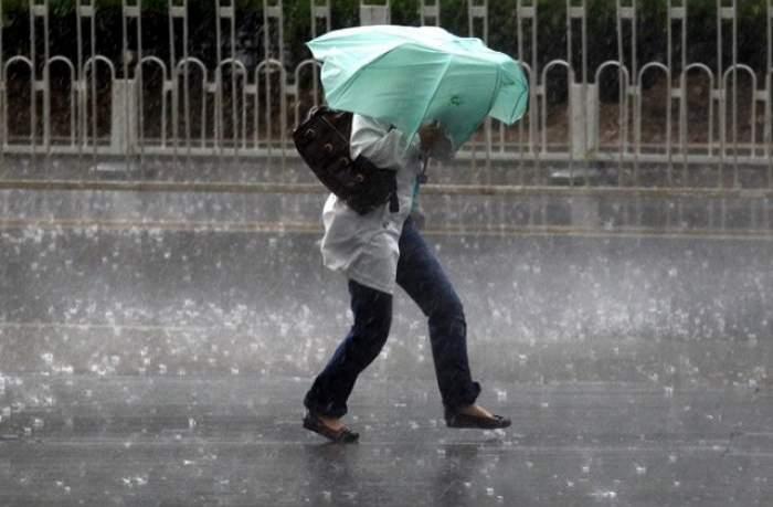 O femeie care merge cu umbrela prin vilejie și grindină