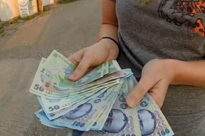 O femeie cu mai mulți bani în mână