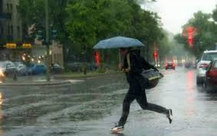 O femeie care traversează strada cu umbrela în mână