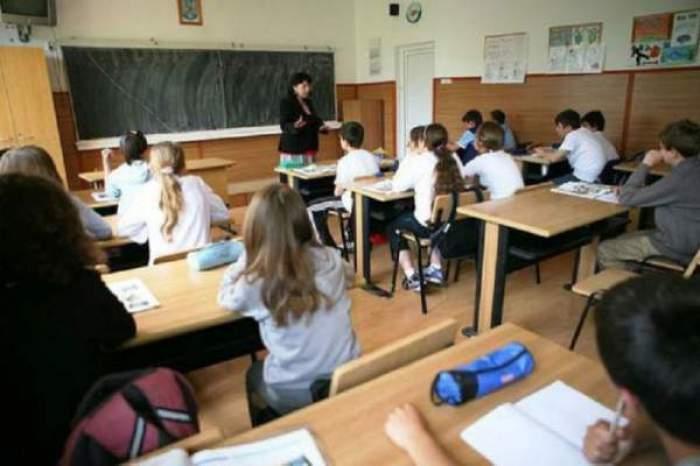 O sală de clasă plină, cu profsorul lângă tablă