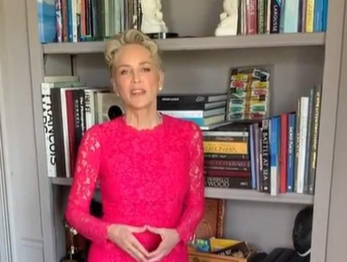Sharon Stone îmbrăcată într-o rochie roz lângă un dulap cu cărți