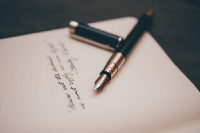 un stilou lăsat pe o foaie de hârtie