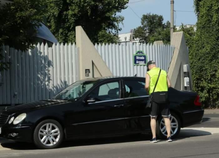 Octavian Bellu, în tricou galben și pantaloni scurti, lângă mașină