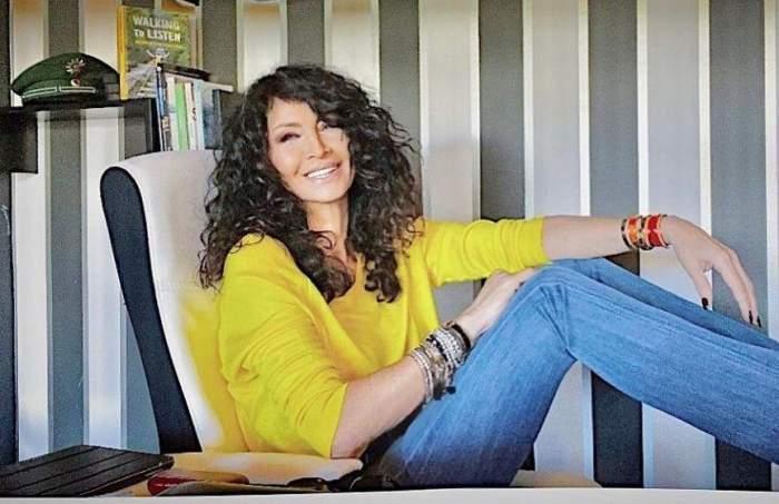Mihaela Rădulescu, cu picioarele pe birou, zâmbitoare