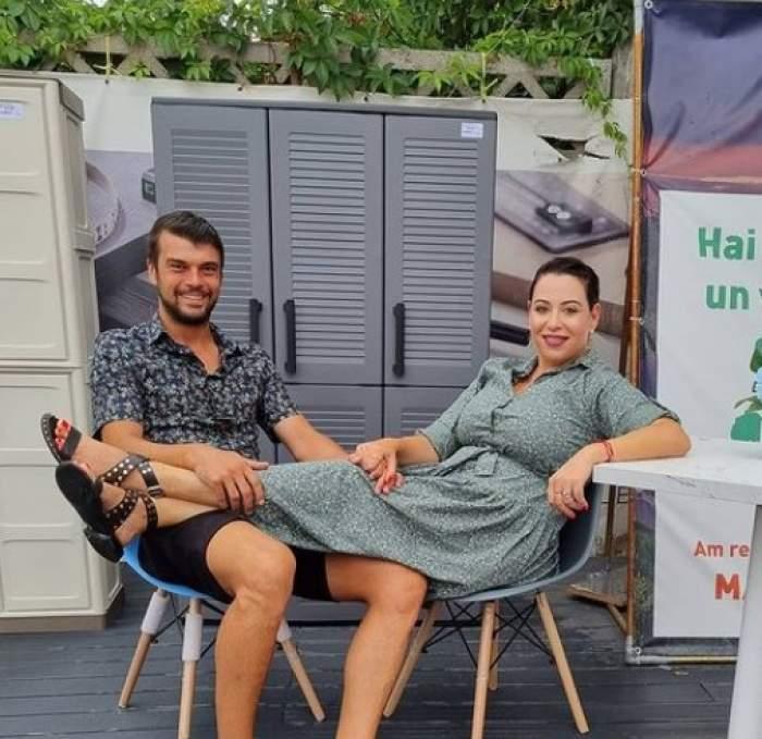 Marius Elisei și Oana Roman așezați pe scaune, ea își ține picioarele în poala lui