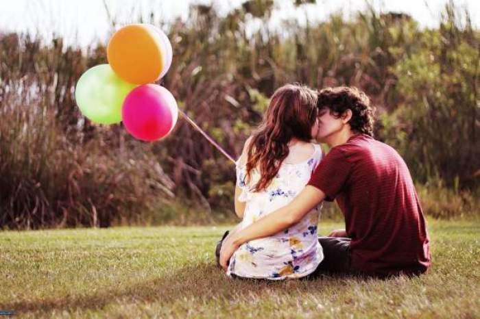 Un cuplu care se pupă pe câmpie, cu baloane în mână