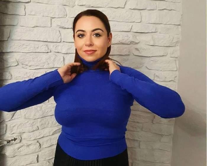 Oana Roman, îmbrăcată în albastru, cu mâinile în păr