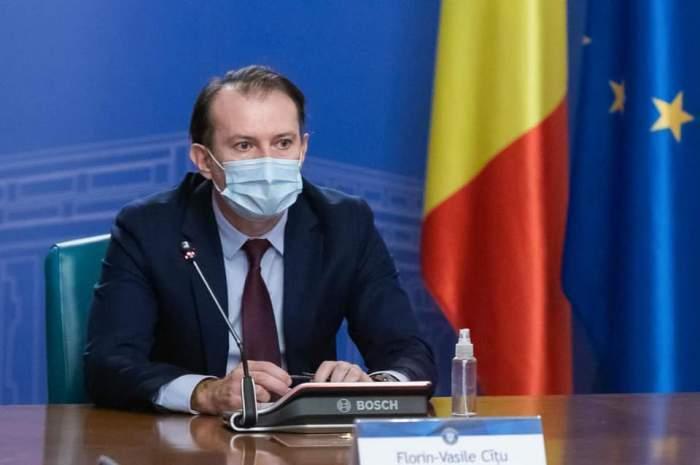 Florin Cîțu, în costum cu mască de protecție pe față, la ședință
