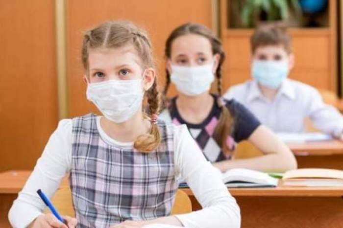Elevi cu masca de protecție pe față