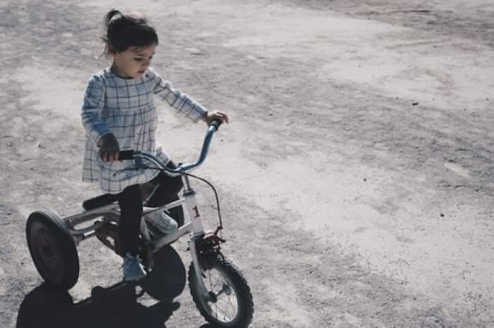 O fetiță pe o bicicletă