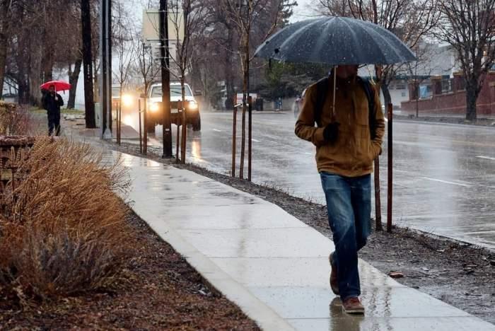 Un bărbat care merge cu umbrela în mână, pe trotuar, plouă